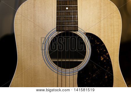 Close up of the sound hole and pick guard of an acoustic guitar.