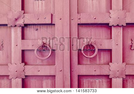 Metal pink aged textured door with rings door handles and metal details in form of stylized flowers. Metal architecture background.
