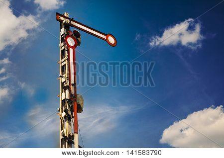 Old retro style railway semaphore against blue sky