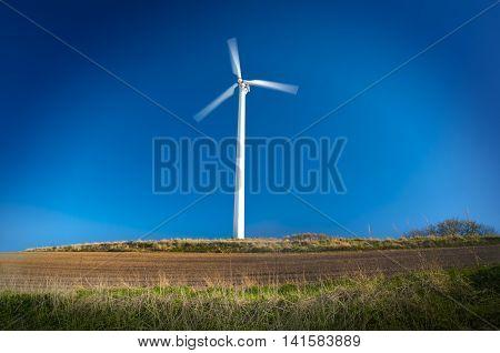 Wind turbine in motion on rural landscape