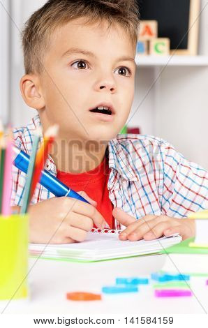 Young boy sitting at desk in the classroom, doing homework at the table - back to school concept.