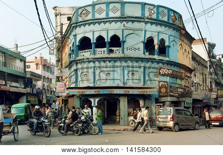 LUCKNOW, INDIA - JAN 31, 2013: Many bikes and people driving on the street with old houses of business area on January 31, 2013. Lucknow with population of 6000455 is the largest city of Uttar Pradesh.