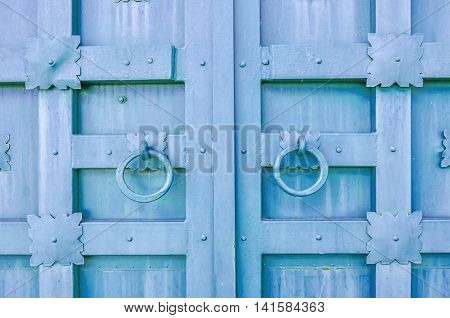 Metal aged pale violet textured door with rings door handles and metal details in form of stylized flowers. Metal architecture background.