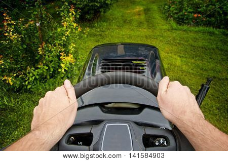 Man driving a mower tractor in garden - point of view shot mowing grass
