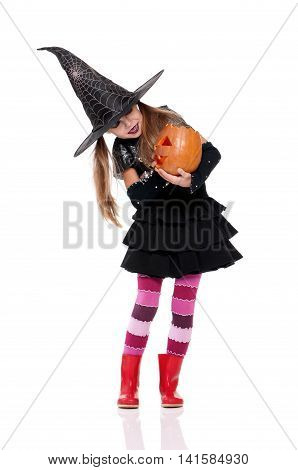 Halloween witch with a magic pumpkin. Beautiful little girl in witches hat and costume holding carved pumpkin, isolated on white background