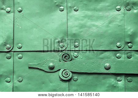 Metal green surface of old hammered metal plates with metal rivets and architectural details on them. Metal blue industrial background.