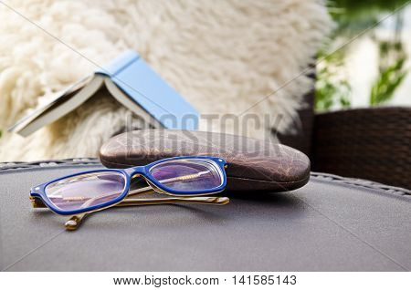 Outdoor shot - glasses for reading with book in the background