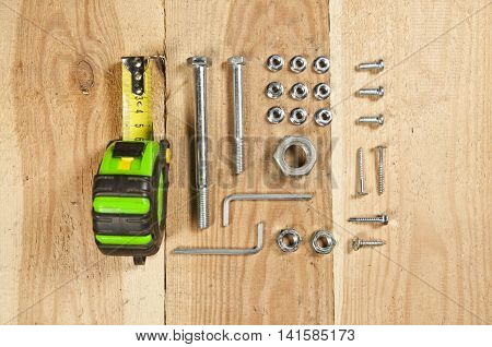 Do it yourself - screws nuts tape measure carpenter tools arranged orderly on wooden table. Top view.