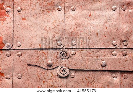 Metal light orange rusty surface of old hammered metal plates with metal rivets and architectural details on them. Metal bright blue industrial background with peeling paint.