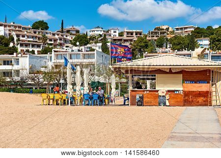 Tossa de Mar Spain - April 7 2016: People sitting in a beach cafe of Tossa del Mar Costa Brava. Catalonia Spain