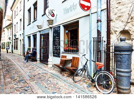 Riga Latvia - July 19 2016: Narrow street of Old Riga. Street lined with a little souvenir shops restaurants and cafes
