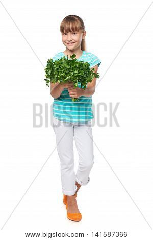 Happy smiling elementary school age girl standing in full length and showing fresh parsley, over white background
