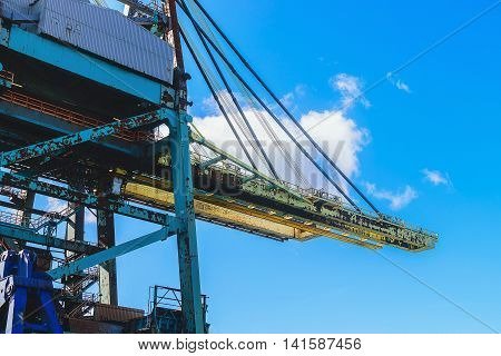 Cargo cranes in jetty over blue sky background.