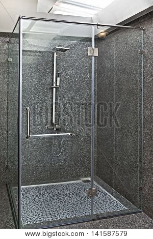 Modern shower cubicle with grey walls with transparent walls