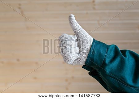 Hand In Gloves Thumbs Up On  Wooden Planks Background