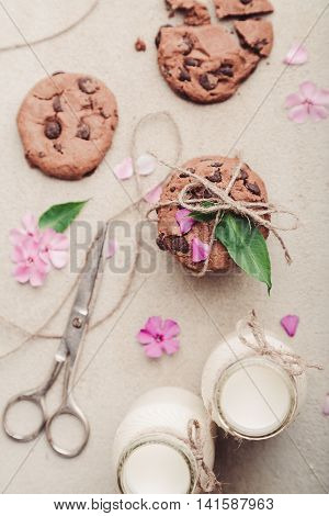 Pile of chocolate chip cookies with two bottles of milk, pink flowers and scissors on rustic grey table, top view