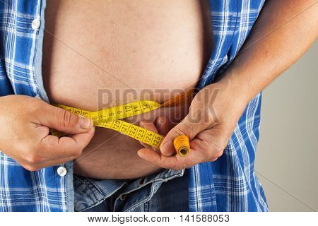 Obese fat man. Man is holding his too fat tummy. Obesity health hazard.