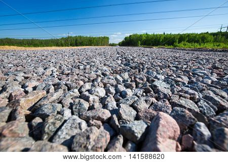 Unfinished Asphalt Country Road In Pine Forest. Breakstone Paving
