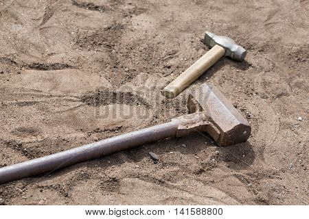 Hammer and sledgehammer on sand outdoors. Construction concept