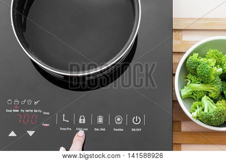 Woman Showing On Child Lock Button On Induction Stove