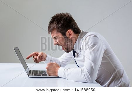 the young man is nervous and poke a finger. It uses a computer while sitting at a table. Office clothing