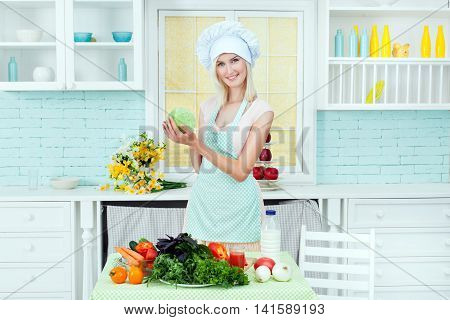 The girl in an apron and the cook's cap in kitchen cooks food from vegetable products. She is a vegetarian.