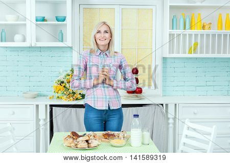 Young girl in kitchen cooks pastries holds a nimbus for dough in hand.