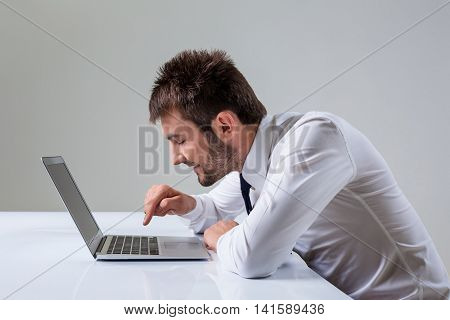 young man presses the keyboard on a laptop bully. It uses a computer while sitting at a table. Office clothing