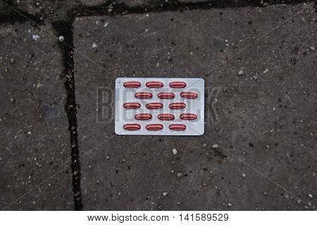 Unmarked Pills Medicine On Ground Stone Tile Sidewalk Texture