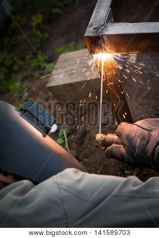 Worker In Protective Mask Welding Steel Railings Outdoors