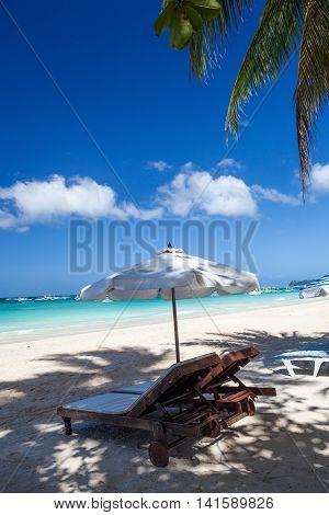 Sun Umbrella And Sunlongers On Tropical Beach