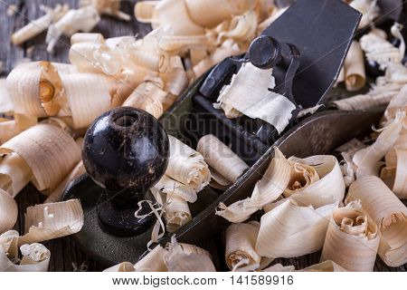 Planer and sawdust on wooden background. Construction concept