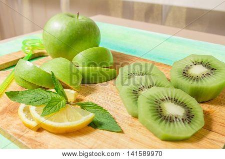Apple, Kiwi, Lemon And Mint On Wooden Board