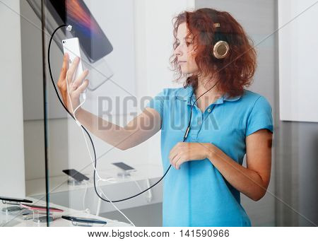 Young ginger woman in the headphones looking at smartphone screen in bobile store making selfie picture through the glass of the shopwindow