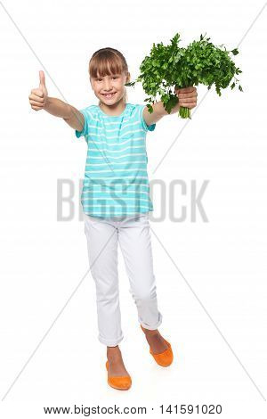 Happy smiling little girl standing in full length, showing fresh parsley, and gesturing thumb up, over white background