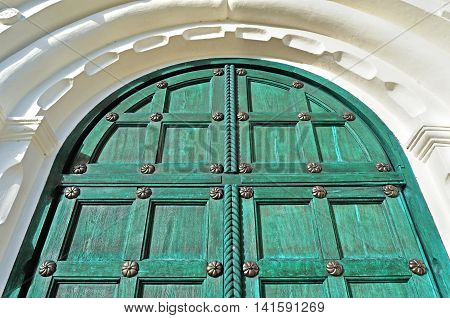 Architecture detailed background - aged wooden door of green color with metal rivets and upper arch of white stone - vintage architecture background