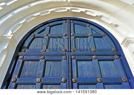 Architecture detailed background - aged wooden door of dark blue color with metal rivets and upper arch of white stone - vintage architecture background