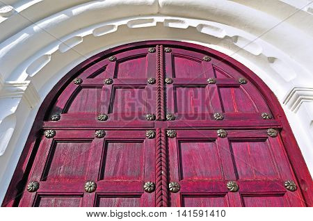 Architecture detailed background - aged wooden door of red color with metal rivets and upper arch of white stone - vintage architecture background
