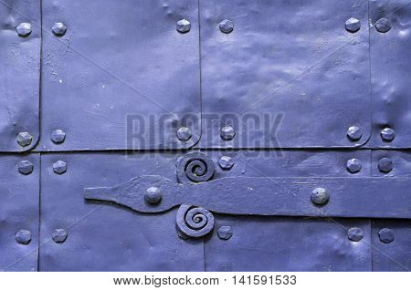 Architecture detailed background - aged wooden door of violet color with metal rivets and upper arch of white stone - vintage architecture background