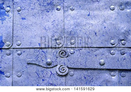 Metal light violet background of old hammered metal plates with metal rivets and architectural details on them. Metal bright blue industrial background with peeling paint.