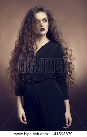 Woman in studio with blowing hairs in wind on brown background