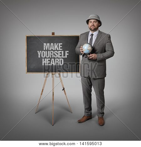 Make yourself heard text on blackboard with businessman holding globe in hands