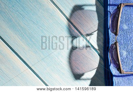 stylish sunglasses and towel on blue wooden table with sunlight