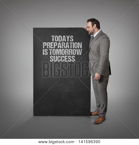 Todays preparation is tomorrow success text on blackboard with businessman standing side
