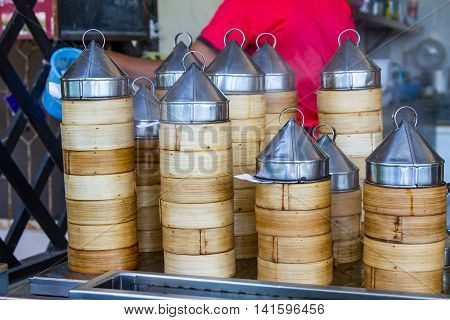 Dumplings cooking inside traditional bamboo steamers in outdoor restaurant