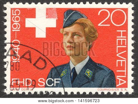 MOSCOW RUSSIA - CIRCA APRIL 2016: a post stamp printed in SWITZERLAND shows a woman in uniform of the FHD dedicated to Women's Emergency Service circa 1965
