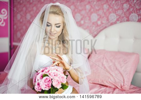 Beautiful sexy young women underwear sitting on a bed with a bouquet of flowers in hands and with a veil on her head. Last preparations for the wedding. Morning the bride.