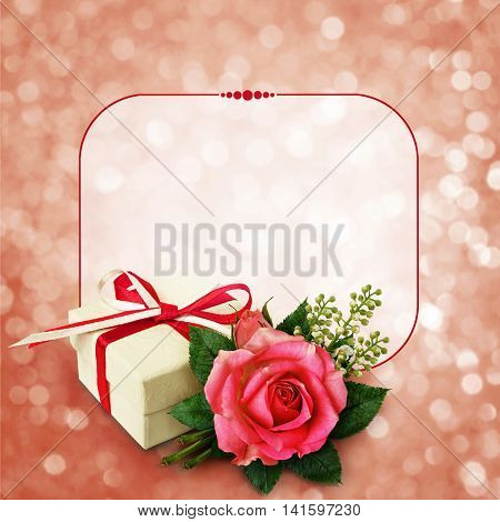 Pink rose flower arangement and a gift on pink holiday background and a frame