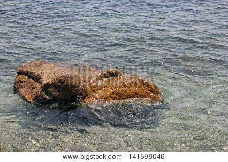 beautiful wet bright small stone rock in blue limpid Black sea water
