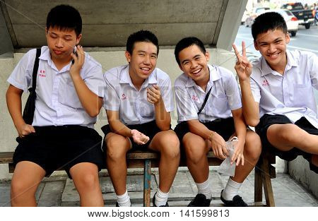Bangkok Thailand - December 23 2009: Four Thai schoolboys in their standard white shirt with navy blue shorts uniforms seated on Silom Road
